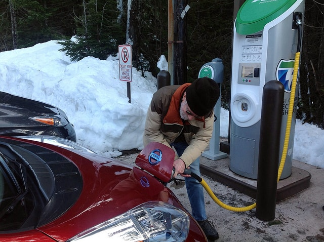 A man charges his electric vehicle
